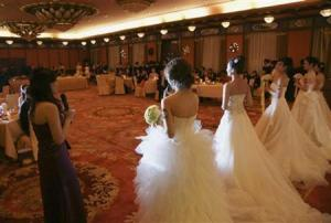 Single women wear wedding dresses during a matching-making ball with Chinese male billionaires in Beijing
